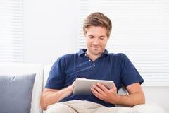 Homem de sorriso que usa a tabuleta digital no sofá Foto de Stock Royalty Free