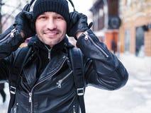 Homem de sorriso walkin a rua do inverno e pela escuta a música através dos fones de ouvido Fotografia de Stock Royalty Free