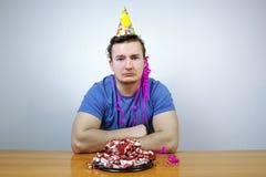 Homem de Sorrorful com o chapéu do cone da festa de anos na cabeça e para amarrotar o bolo, gritando indivíduo no humor mau ao te imagem de stock