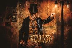 Homem de Steampunk com a bobina de Tesla no fundo do steampunk do vintage foto de stock