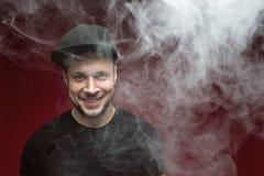 Homem de Vaping e uma nuvem do vapor Imagem de Stock