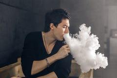 Homem de Vaping que guarda uma modificação Uma nuvem do vapor Fundo preto Imagens de Stock