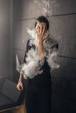 Homem de Vaping que guarda uma modificação Uma nuvem do vapor Fundo preto Imagem de Stock Royalty Free