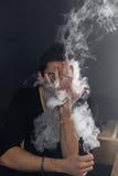 Homem de Vaping que guarda uma modificação Uma nuvem do vapor Fundo preto Foto de Stock Royalty Free