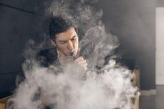 Homem de Vaping que guarda uma modificação Uma nuvem do vapor Fundo preto Imagem de Stock