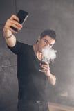 Homem de Vaping que guarda uma modificação Uma nuvem do vapor Fundo preto Foto de Stock