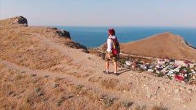 Homem de viagem com uma trouxa e uma câmera, andando através das montanhas, com uma grande vista das montanhas e filme