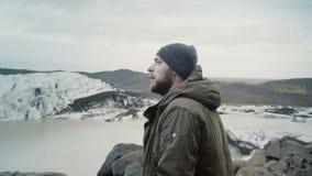 Homem de viagem novo que está na parte superior da montanha e que olha em geleiras na lagoa do gelo de Vatnajokull em Islândia video estoque