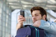 Homem de viagem que espera na estação e em olhar o telefone celular fotografia de stock royalty free
