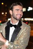 Homem de vista luxuoso no sorriso dourado sparkly do smoking Foto de Stock