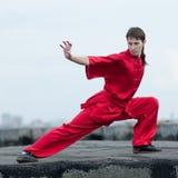 Homem de Wushoo na arte marcial vermelha da prática Imagens de Stock Royalty Free