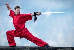 Homem de Wushoo na arte marcial vermelha da prática fotos de stock royalty free