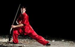 Homem de Wushoo na arte marcial vermelha da prática Foto de Stock Royalty Free