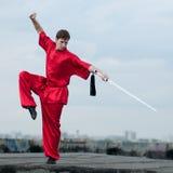 Homem de Wushoo na arte marcial vermelha da prática Fotografia de Stock