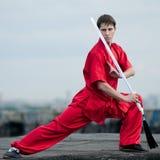 Homem de Wushoo na arte marcial vermelha da prática Imagem de Stock
