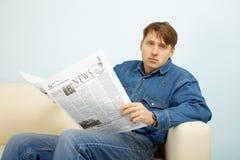Homem decepcionado com notícia do jornal Fotografia de Stock