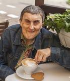 Homem deficiente com a paralisia cerebral que senta-se no café exterior Imagens de Stock
