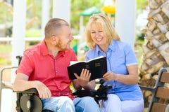 Homem deficiente com seu fiilng da esposa feliz ao ler a Bíblia Sagrada Fotografia de Stock Royalty Free