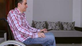 Homem deficiente dos jovens que olha a tevê video estoque