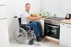 Homem deficiente em pratos de lavagem da cadeira de rodas fotos de stock royalty free