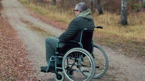 Homem deficiente na cadeira de rodas no auxílio de espera da estrada vídeos de arquivo