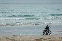 Homem deficiente na cadeira de rodas na praia que olha o telefone celular Fotografia de Stock