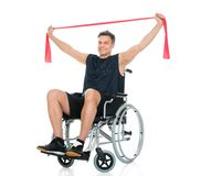 Homem deficiente na cadeira de rodas que exercita com faixa da resistência fotos de stock