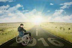 Homem deficiente na estrada com números 2016 Imagens de Stock Royalty Free
