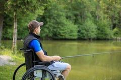 Homem deficiente na pesca da cadeira de rodas no lago foto de stock royalty free