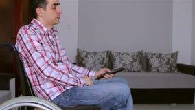 Homem deficiente novo na televisão de observação da cadeira de rodas video estoque