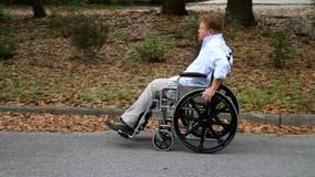 Homem deficiente que usa a bandeja da cadeira de rodas filme