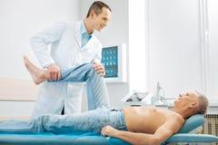 Homem deleitado alegre que encontra-se na cama da massagem fotografia de stock