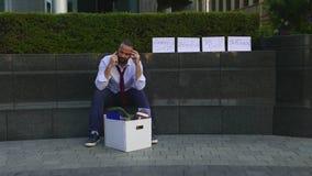 Homem demitido, rastroenny que senta-se na rua, uma caixa com artigos pessoais Em torno do cartão decomposto com video estoque