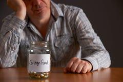 Homem deprimido que olha o frasco vazio etiquetado fundo da faculdade Foto de Stock