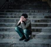 Homem deprimido que senta para fora lateral nas etapas que sentem cansados e tristes Foto de Stock