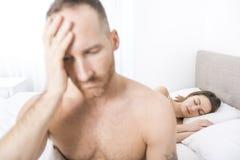 Homem deprimido que senta-se na borda da cama no quarto imagens de stock