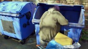 Homem desabrigado com carrinho de compras que escava no balde do lixo vídeos de arquivo