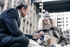 Homem desabrigado miserável sujo que toma a nota de dólar das mãos do homem amável fotografia de stock royalty free