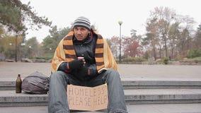 Homem desabrigado na roupa gasto que senta-se no parque da cidade com sinal que pede a ajuda vídeos de arquivo