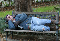 Homem desabrigado no banco - completamente - vista fotografia de stock