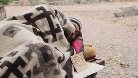 Homem desabrigado pensativo que encontra-se no banco no parque com sinal da ajuda Pedido, pobreza vídeos de arquivo