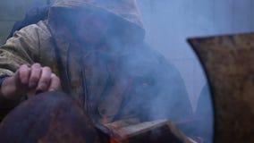 Homem desabrigado que aquece suas mãos por um fogo filme