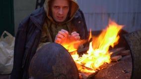 Homem desabrigado que aquece suas mãos por um fogo video estoque