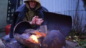 Homem desabrigado que aquece suas mãos por um fogo vídeos de arquivo