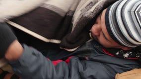 Homem desabrigado que dorme em um banco, em uma pessoa só congelada, em uma pobreza e em uma miséria vídeos de arquivo