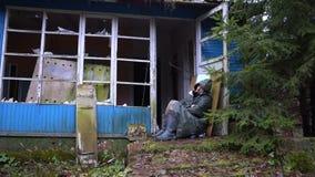 Homem desabrigado que dorme no ar livre no patamar de uma casa arruinada abandonada filme