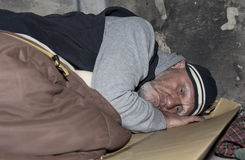 Homem desabrigado que dorme no cartão e em um saco-cama velho o fotos de stock royalty free