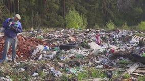 Homem desabrigado que procura artigos e o alimento úteis para a sobrevivência entre desperdícios em montões de lixo da descarga a filme