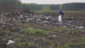 Homem desabrigado que procura artigos e o alimento úteis para a sobrevivência entre desperdícios em montões de lixo da descarga a video estoque