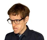 Homem desagradado com vidros na vista de um quarto branca Imagens de Stock Royalty Free